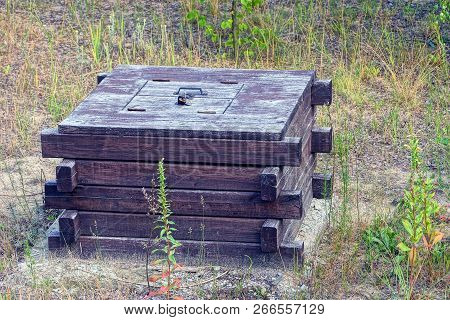 Closed Brown Wooden Square Well In Green Grass