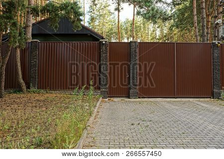Long Metal Brown Fence And Gate At The Sidewalk And Grass Outside