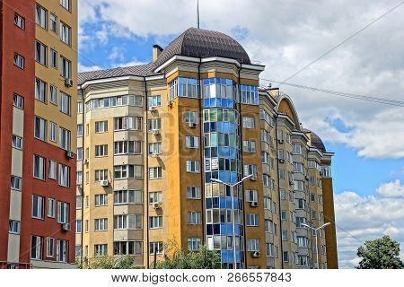 Part Of A Multistory Building With Balconies And Windows Against The Sky And Clouds