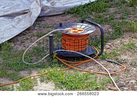 Plastic Carrier With Rosettes And Orange Cable On Green Grass