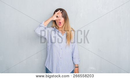Young adult woman over grey grunge wall wearing fashion business outfit doing ok gesture shocked with surprised face, eye looking through fingers. Unbelieving expression.