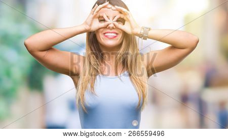 Young beautiful elegant business woman over isolated background doing ok gesture like binoculars sticking tongue out, eyes looking through fingers. Crazy expression.