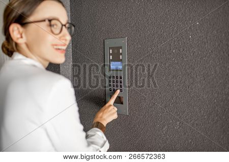 Young Business Woman In White Suit Entering Code On The Intercom Keyboard Of The Residential Modern