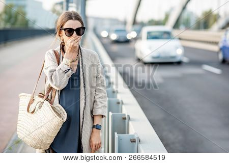 Woman Closing Her Nose Feeling Bad Because Of The Air Pollution On The Bridge With Traffic In The Ci