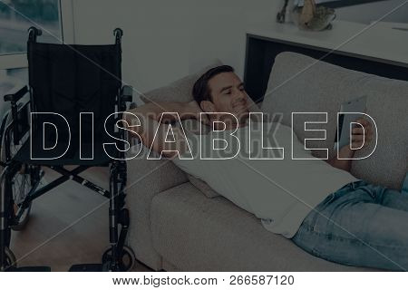 Disabled Man. Man Lying On Sofa. Wheelchair On Background Of Man. Man Watching Video. Video On Table