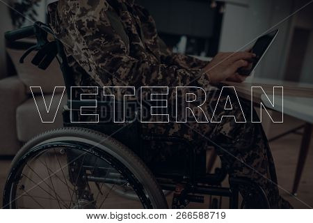 Military Veteran. Disabled Man In A Wheelchair. Man Sitting At Table. Man Using S Tablet Pc. Man Typ