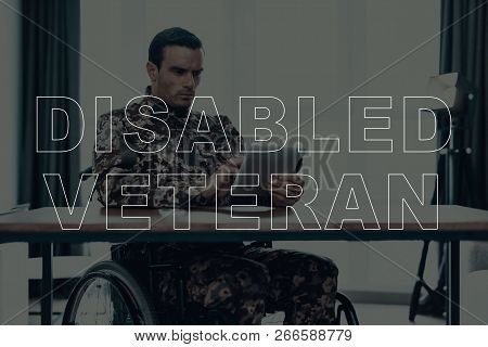 Military Veteran. Disabled Man In A Wheelchair. Man Sitting At Table. Man Using Tablet Pc. Man Is So