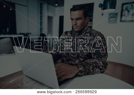 Military Veteran. Man Sitting At Table. Man Using Laptop. Man Is Soldier. Soldier In Military Unifor