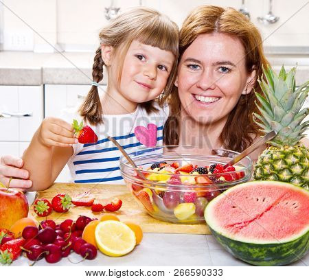A Mother Gives To The Little Girl A Fruit Salad In The Kitchen.