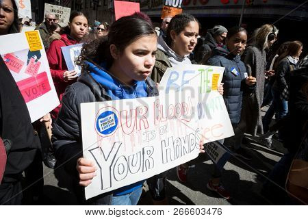 March For Our Lives: A young woman marches holding a sign that says Our Blood Is On Your Hands during the march to end gun violence on 6th Ave, NEW YORK MAR 24 2018.