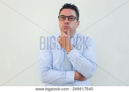 Pensive Handsome Businessman Rubbing Chin And Looking At Camera. Thoughtful Middle-aged Male Manager