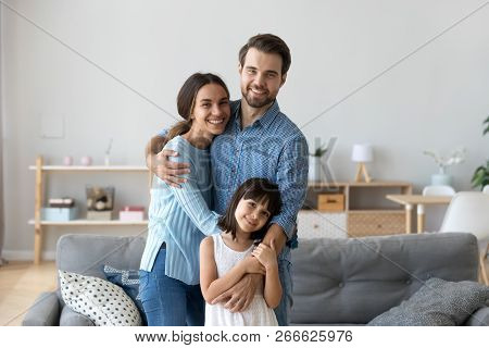 Whole Family Standing In Living Room Embracing Looking At Camera