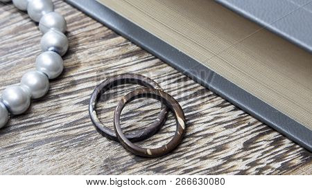 Unique handmade coconut rings in wooden background with props. Artisan wedding ring bands. Love and union concept. poster