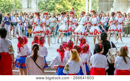 Kharkiv, Ukraine - 17 May 2018 : crowd of people looking at girls in white dresses with ukrainian national attributes dancing on embroidered shirt holiday in Kharkiv