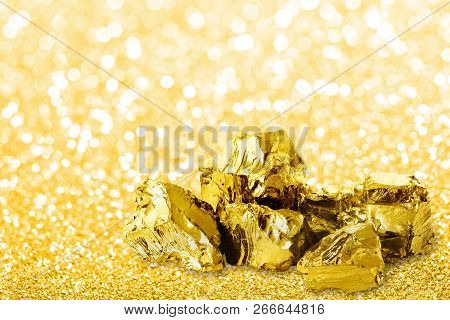 Golden Ingots Close Up On Golden Dust Glitter Background. Shiny Golden Nuggets On Golden Glitter Bac