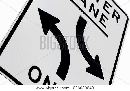 Abstract Center Lane Ends Sign With Trees, Road, And A Warehouse In The Background
