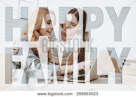 Happy Family. Mother Sitting At Table. Daughter Standing Near Mother. Mother Working On Laptop Compu