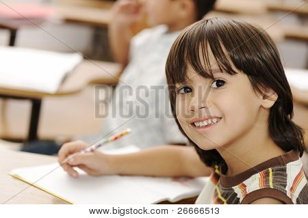 Cute positive boy writing and smiling. Indoor, school, classroom.
