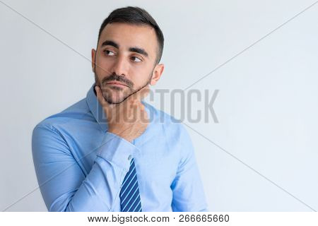 Pensive Handsome Young Male Manager In Blue Shirt Touching Chin And Looking Away. Confident Business