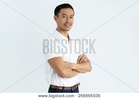 Content Confident Handsome Asian Businessman Looking At Camera And Standing Against White Background