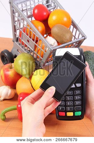 Using Credit Card Reader, Payment Terminal With Mobile Phone With Nfc Technology And Fresh Fruits An