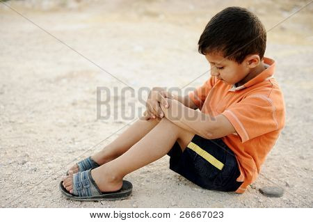 Hungry kid begging on the street with a crutches beside