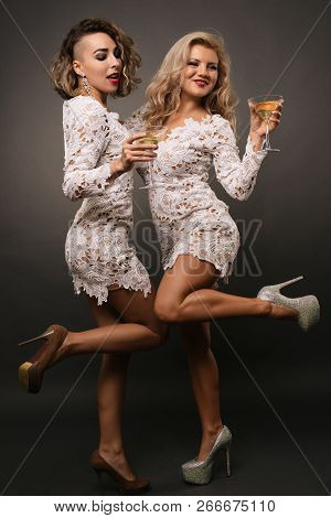 Two Beautiful Young Women Girlfriends In White Short Dress Dance With Martini Glasses Isolated