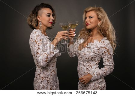 Two Beautiful Young Women Girlfriends Celebrate The Holiday With Martini Glasses Isolated