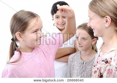 Girls measuring height, group playing