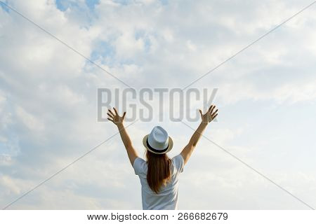Young Girl In Hat With Hands Up, Back View, Background Blue Sky In The Clouds, Place For Text Copy S