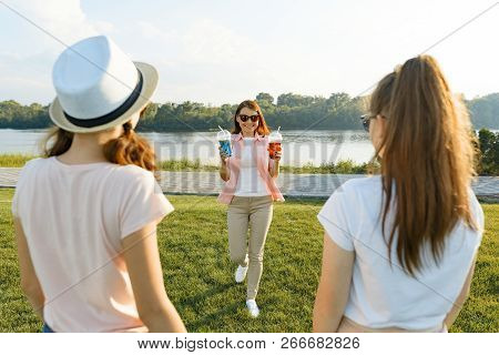 Happy Mother Resting On Nature With Her Teenage Daughters 14 And 16 Years Old. Communication Of Pare