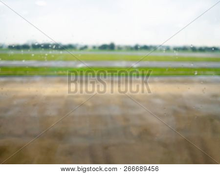 Blur Runway Airport View From Airplane Window In Rain Day.