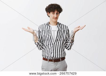 Waist-up Shot Of Clueless Good-looking And Funny Unaware Guy With Moustache And Curly Dark Hair Shru