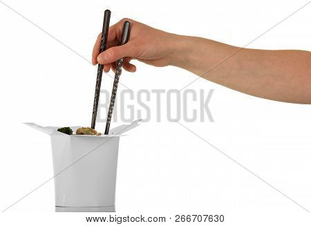 Female Hand Holding Chopsticks Pulls The Noodles Out Of The Box Wok Isolated On White Background