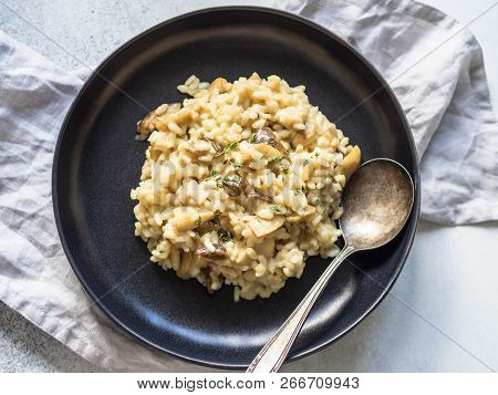 Italian Risotto With Porcini Mushrooms And Fresh Thyme In A Black Plate On A Gray Background. Homema