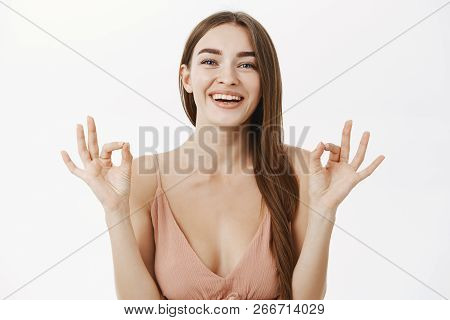Waist-up Shot Of Optimistic Happy European Gorgeous Female In Trendy Beige Dress Showing Okay Or Per