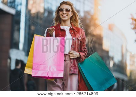 Shopping Woman Walking Outside At Street Holding Shopping Bags. Shopper Smiling Happy Walking The St