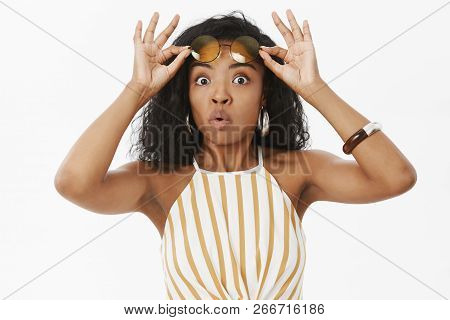 Portrait Of Amazed And Curious Young African American Female Taking Off Sunglasses Folding Lips Whis