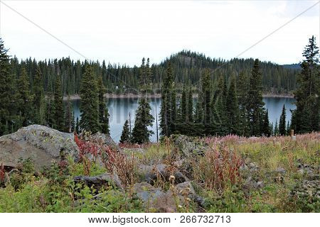 A Clear, Cold Alpine Lake Is Visible Below A Rocky Overlook On Grand Mesa.