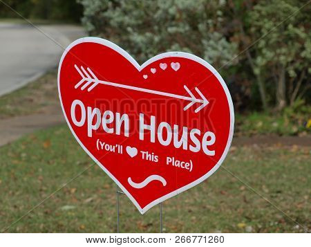 A Sign Alongside A Busy Street Directs Future Homeowners To An Open House In The Neighborhood. The H