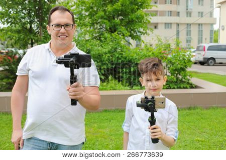 Boy and man shoots video by gimbals and phones on green grass outdoor