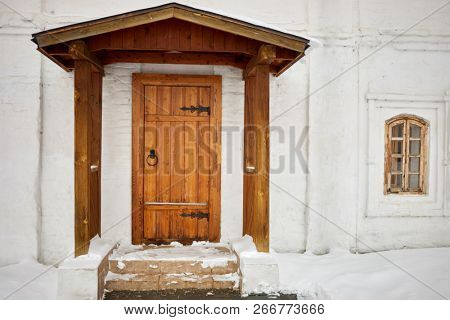 Porch with wooden canopy, entrance wooden door in old house, winter day.