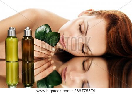 Beautiful young woman with grean leaves. Organic beauty concept. Bottles with essential oils at foreground.