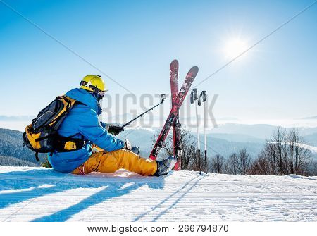 Rearview Shot Of A Skier Sitting On The Snow On Top Of The Mountain Taking Selfies With His Action C