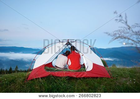 Rear view of a young couple sitting in a tent looking at the mountains in the morning haze at dawn under a blue sky on which the moon is shining in the distance. poster