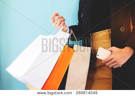 Woman In Black Overcoat With Shopping Bag And Smartphone In Hands. Black Friday