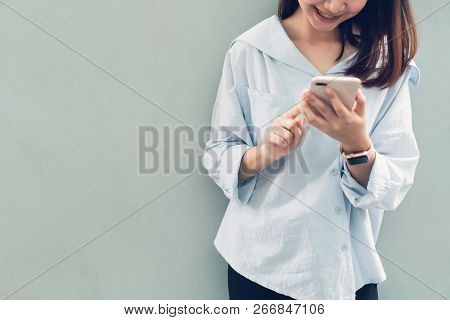 Woman Using Smartphone, During Leisure Time. The Concept Of Using The Phone Is Essential In Everyday