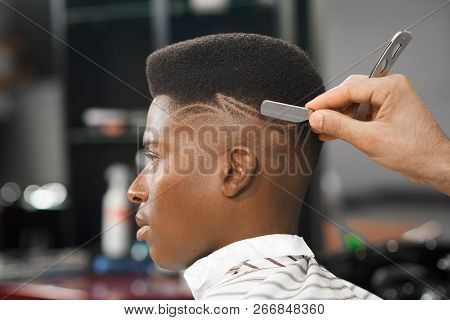 Side View Of Serious Man With Stylish Modern Haircut Looking Forward In Barber Shop. Hand Of Barber