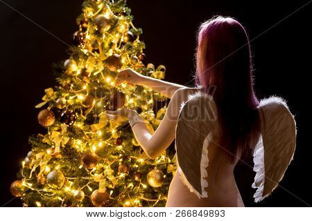 Angel And Spruce With Decorations. Young Woman Decorates The Golden Christmas Tree. Girl And Adornme