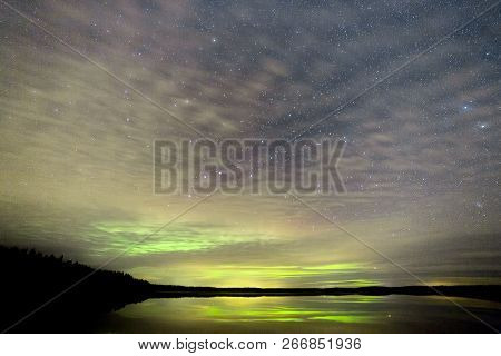 Northern Lights Over Lake With Clouds And Stars.